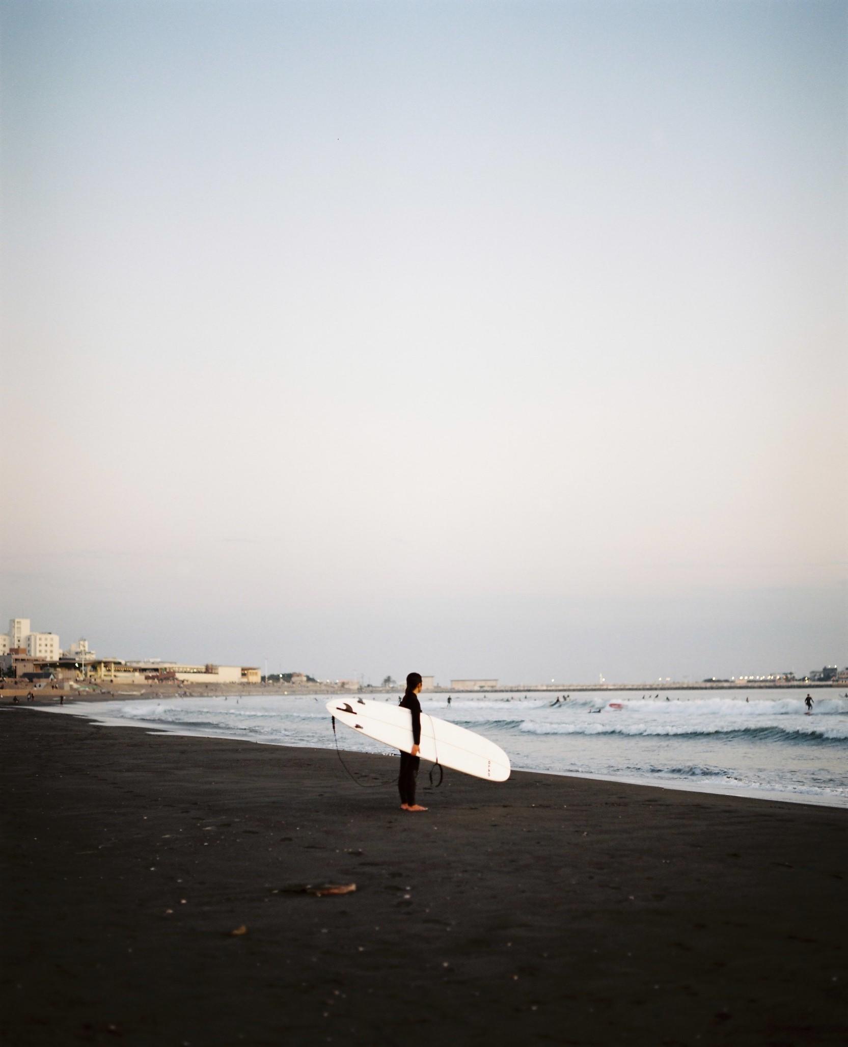 鵠沼海岸とサーファーの女性
